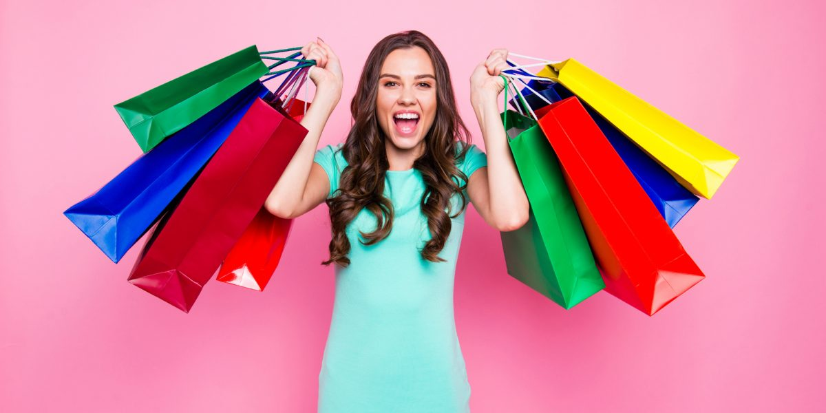 Time of big discounts! Crazy brunette girl with long dark hair holds colorful shopping bags isolated on bright pink background