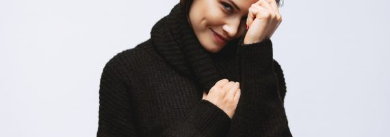 Portrait of pretty woman looking at camera and smiling. Female model in black sweater on white background.